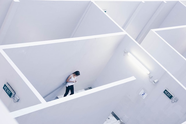 Woman texting in a white maze
