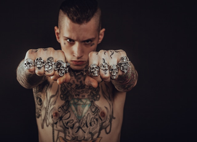 Man with tattoos bearing fists covered in rings