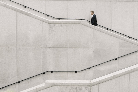 Man in business suit ascending long staircase