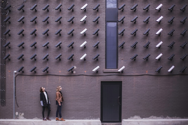 Two women being watched by a wall of cctv cameras
